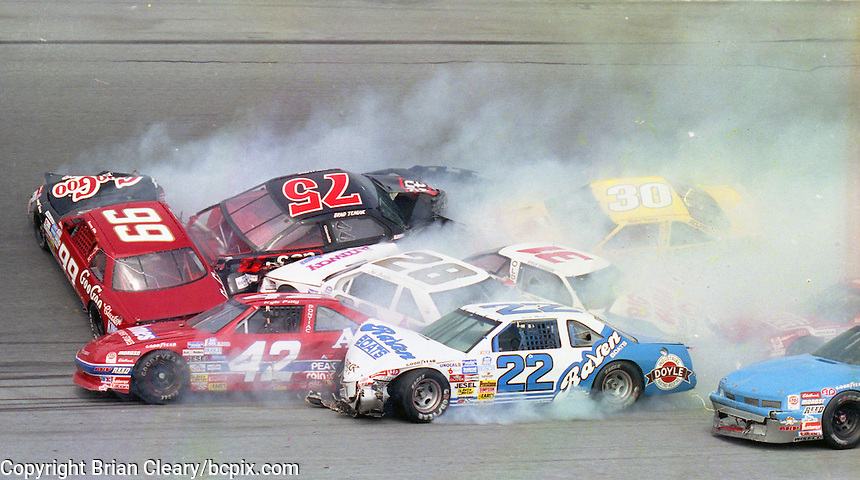 The cars of Tommy Ellis (99), Brad Teague (75), Hut Stricklin (28), Kyle Petty (42), Rick Mast (22), Steve Grissom (31), Michael Waltrip (30) , and Tom Peck (96) are among the cars involved in one of the biggest crashes in the history of Daytona Internationa Speedway , a 24 car accident during the Goody's 300, NASCAR Busch Series, Daytona Beach, FL, February 17, 1990.  (Photo by Brian Cleary/www.bcpix.com)
