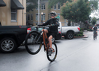 NWA Democrat-Gazette/CHARLIE KAIJO Jackson Horton, 15, of Bentonville (left) pops a wheelie on his bike while riding with friends after a brief downpour, Sunday, October 7, 2018 at the downtown square in Bentonville.