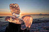 Staged ice chunks catch beautiful backlight as the sun sets behind Mount Redoubt, Mount Iliamna and the Aleutian Range as seen from the beach in Kemai, Alaska.