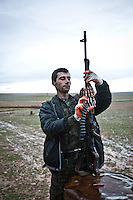 SYRIA: A YPG fighter checks the load of his weapon before going on the front line near the cement plant.<br /> <br /> SYRIA: Un combattant YPG vérifie le chargement de son arme avant de rendre sur la première ligne de front près de la cimenterie.