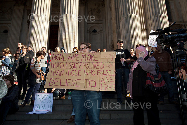 "London, 15/10/2011. St Paul's Square became the stage of the UK arm of the ""Occupy"" protest movement which has been growing around the world. The Occupy movement is a world-wide protest against the financial crises created by the actual financial system, by speculation, by deregulation, and by the actions of major international financial and investment banks. Around 2,000 protesters armed with tents and placards, gathered outside the famous Cathedral intending to occupy Paternoster Square, home of the London Stock Exchange and the heart of the City of London, but they were hampered by City police officers. After this failed attempt the protesters decided to camp in front St Paul's where the situation with police forces became immediately tense. Masked like the character of Guy Fawkes from the movie ""V for Vendetta"", Julian Assange appeared on the square to give a speech in support of the protesters. During the late evening police forces heavily armed with riot control equipment charged the square, attempting to evict the occupants who resisted. Later in the evening the police retreated and the occupation continued peacefully."