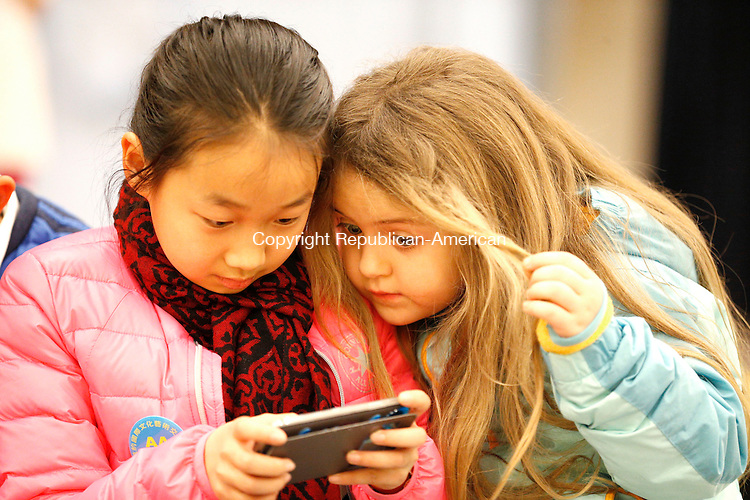 Waterbury, CT- 12 February 2015-021215CM01- Baoyi Han, 11, left, an exchange student from China plays a video game with Kayleigh Gorman, 6, a 1st grade student at Carrington Elementary School in Waterbury on Thursday. The pair were playing a popular video game, titled Minecraft.  School officials held activities and entertainment for the exchange students, including a pajama movie night.    Christopher Massa Republican-American