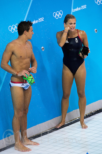 26 JUL 2012 - LONDON, GBR - Diver Tom Daley (GBR) watches Great Britain team mate Tonia Couch (GBR) pretending to make a telephone call as they showered after finishing their practice sessions at the Aquatics Centre in the Olympic Park in Stratford, London, Great Britain  ahead of the start of the London 2012 Olympic Games .(PHOTO (C) 2012 NIGEL FARROW)