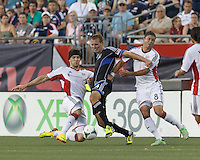 New England Revolution defender Stephen McCarthy (15) and New England Revolution defender Chris Tierney (8) double team dribbling San Jose Earthquakes forward Adam Jahn (14). In a Major League Soccer (MLS) match, the New England Revolution (white) defeated San Jose Earthquakes (black), 2-0, at Gillette Stadium on July 6, 2013.