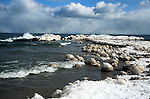 Balls of ice float in a cold Feburary Lake Superior near the beach by north side of the Marquette Harbor Light