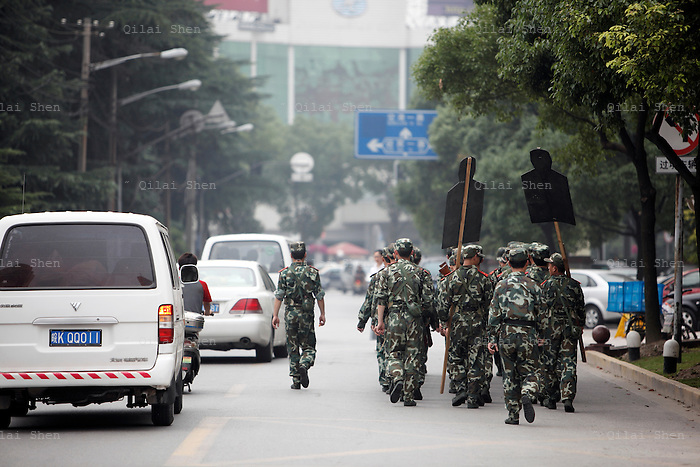 Chinese People's Liberation Army (PLA) soldiers guarding the airport walk in formation on their way to a target practice in Shanghai, China on 15 June 2009.