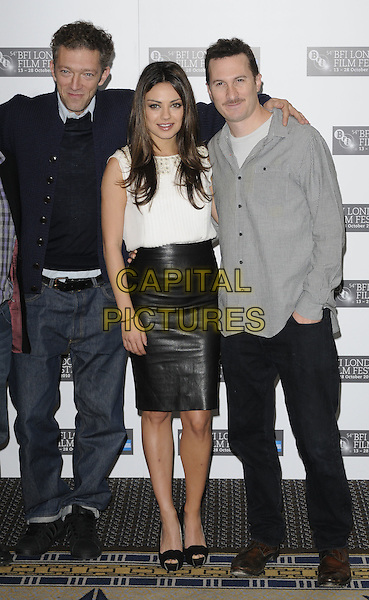 "VINCENT CASSEL, MILA KUNIS & DARREN ARONOFSKY.The ""Black Swan"" press conference & photocall, London Film Festival, Day 10, Berkeley hotel, London, England..October 22nd, 2010.LFF full length black leather skirt platform peep toe shoes white sleeveless top coat jacket navy jumper sweater top blue jeans denim shirt trainers sneakers.CAP/CAN.©Can Nguyen/Capital Pictures."