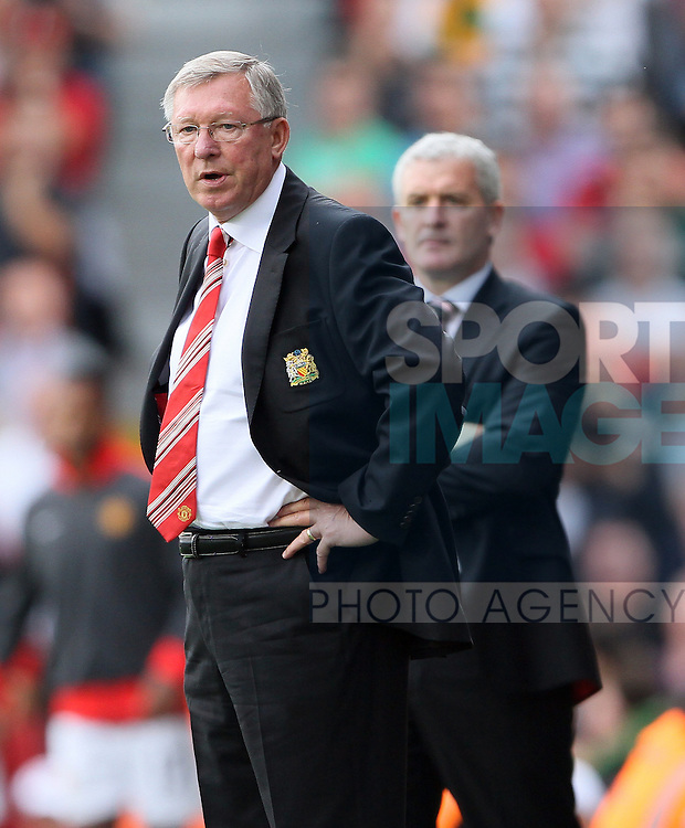 Manchester United's Sir Alex Ferguson looks on with Mark Hughes in the background