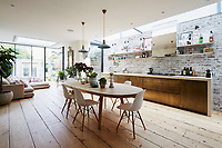 The kitchen is an impressive, open-plan space incorporating a dining table and chairs and a seating area by the patio door. The kitchen cupboards are custom-built by Bert & May and an exposed brick façade, painted to look old, adds an industrial vibe to the kitchen. The kitchen chairs are Eames DSW.