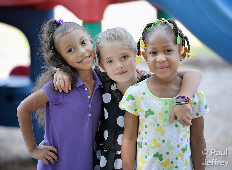 Three girls pose on the playground of the child care center of the Wesley House Community Center in Meridian, Mississippi. Wesley House provides a variety of educational and other services to the community.