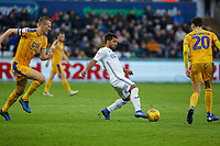 Wayne Routledge of Swansea City (C) against Dan Burn (L) and Kal Naismith of Wigan Athletic (R) during the Sky Bet Championship match between Swansea City and Wigan Athletic at the Liberty Stadium, Swansea, Wales, UK. Saturday 29 December 2018