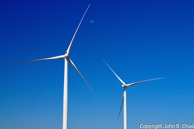 2 wind turbines set against a blue sky with half moon. Taken in eastern Washington State.