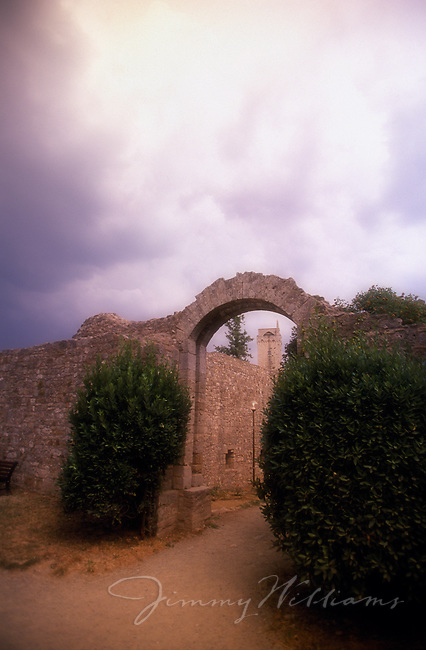 A wide view of an old stone archway at sunset in a small Italian town