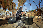 A Somali woman who fled drought and war at home cooks over a fire in a hastily-constructed hut on the outskirts of the Dadaab refugee camp in northeastern Kenya. Tens of thousands of newly arrived Somalis have swelled the population of what was already the world's largest refugee camp.