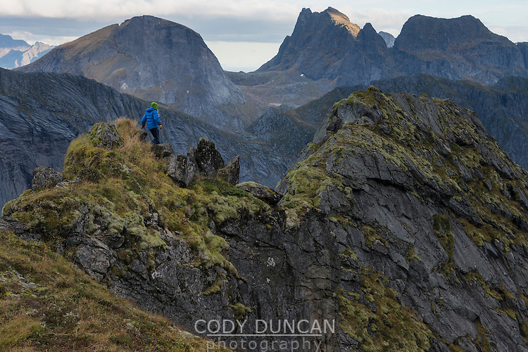 Female hiker walks along narrow ridge near Storskiva mountain peak, Moskenesøy, Lofoten Islands, Norway