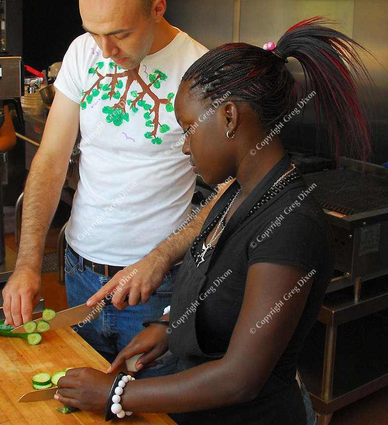 Andrew Glaza, program chef for the Atwood Community Center, teaches Shemekia Graham proper slicing technique on Wednesday, August 20, 2008 in a program in which area youth learn chef skills