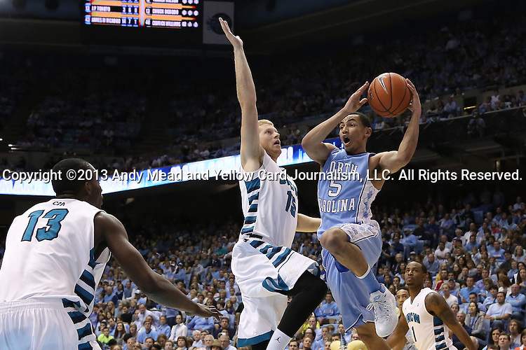 31 December 2013: North Carolina's Marcus Paige (5) is defended by UNC Wilmington's Luke Hager (15) and Chuck Ogbodo (NGA) (13). The University of North Carolina Tar Heels played the UNC Wilmington Seahawks at the Dean E. Smith Center in Chapel Hill, North Carolina in a 2013-14 NCAA Division I Men's Basketball game. UNC won the game 84-51.