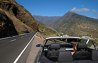 Convertible parked next to empty road with the mountains of La Palma in the background. La Palma, Canary Islands.