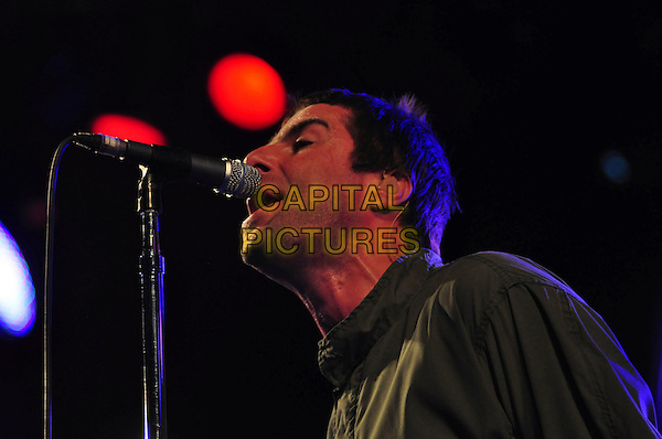 LIAM GALLAGHER of OASIS .Oasis perform on day two of the Roskilde Festival in Roskilde, Denmark, .July 3rd 2009..music concert gig band live on stage playing performing portrait headshot microphone stand pose singing green khaki coat parka profile .CAP/TTL .©TTL/Capital Pictures