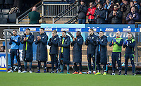 The Wycombe coaching staff and substitutes take part in a minutes applause in memory of Graham Taylor during the Sky Bet League 2 match between Wycombe Wanderers and Yeovil Town at Adams Park, High Wycombe, England on 14 January 2017. Photo by PRiME Media Images.