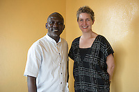 Kabah Trawally of The National Mandingo Caucus of Liberia ambulance company and Occidental College professor Mary Beth Heffernan pose for a photo in Kabah's Jacob's Town, Monrovia office in Liberia, Feb. 28, 2015.<br /> (Photo by Marc Campos, Occidental College Photographer) Mary Beth Heffernan, professor of art and art history at Occidental College, works in Monrovia the capital of Liberia, Africa in 2015. Professor Heffernan was there to work on her PPE (personal protective equipment) Portrait Project, which helps health care workers and patients fighting the Ebola virus disease in West Africa.<br />