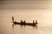 Itaparica Island, Brazil. A dugout canoe with six people in the evening light; Bahia State.