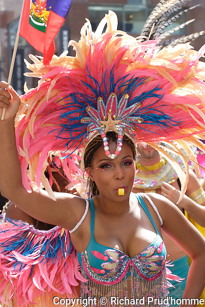 The immensely colorful Carifiesta parade takes over Ste-Catherine street West in downtown Montreal.<br /> <br /> The participants and spectators vibrate and dance to the rhythm of Latin West Indian and Afro-Caribbean music.