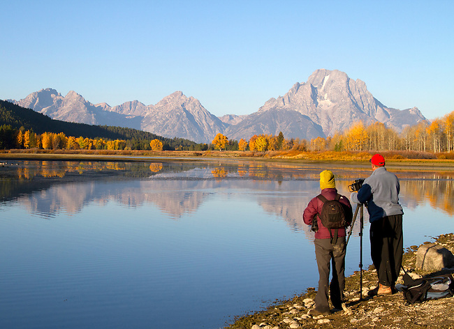 Photographers at the edge of Oxbow bend gazing at Mt. Moran and the fall colors.