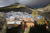 The town of Chefchaouen and its 15th century Kasbah in the foreground, in the Rif mountains of North West Morocco. The Kasbah or fortress served as military camp, seat of power and rulers residence and was used by Ali Ibn Mousa Ibn Rashid in his jihad against the Portuguese. It is surrounded by a wall with 11 defensive towers and a 4-storey watchtower and contains a garden of orange, jasmine and palm trees. It now houses an art gallery and ethnography museum. Chefchaouen was founded in 1471 by Moulay Ali Ben Moussa Ben Rashid El Alami to house the muslims expelled from Andalusia. It is famous for its blue painted houses, originated by the Jewish community, and is listed by UNESCO under the Intangible Cultural Heritage of Humanity. Picture by Manuel Cohen