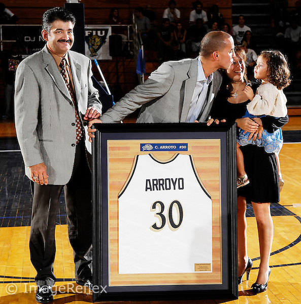 5 January 2008: Orlando Magic point guard Carlos Arroyo (center), standing with Florida International Athletic Director Pete Garcia (left), leans over to kiss his wife and child, Gabriella (right) during the festivities honoring Arroyo by retiring his Florida International jersey number at the half-time of the FIU 69-58 victory over FAU at the Pharmed Arena in Miami, Florida.