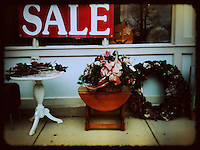 Sale sign with items  for sale outside second-hand store.  iPhone photo. Manipulated with app.