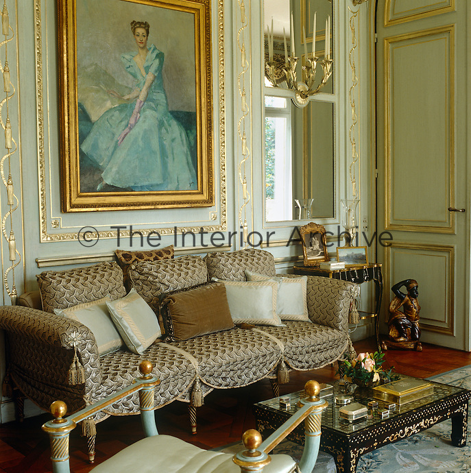 A gilt-framed portrait of the Duchess of Windsor by her protege, Etienne Drian, is mounted on the painted panelling of the salon