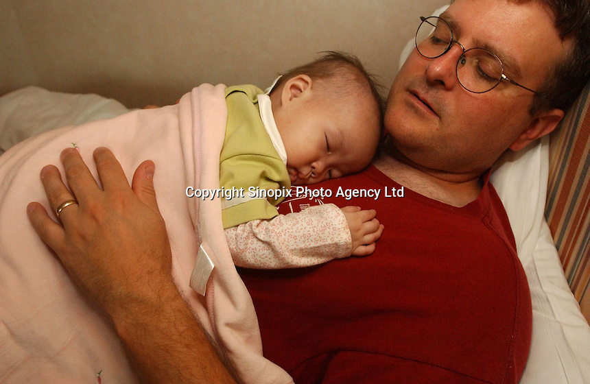 Michael sleeps with newly adopted baby daughter Jensen on his chest during the first 24 hours of the first restless night. The family were part of a group of Canadian nationals go through the adoption procedure in Changsha, Hunan, China.