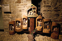 "Switzerland. Canton Tessin. Vira Gambarogno. The old town shows an exhibit of various Nativity scenes, illuminated at night for the Christmas holiday season. A Nativity Scene, may be used to describe any depiction of the Nativity of Jesus in art, but in the sense covered here, also called a crib or in North America and France a crèche (meaning ""crib"" or ""manger"" in French). It means a three-dimensional folk art depiction of the birth or birthplace of Jesus, either sculpted or using two-dimensional (cut-out) figures arranged in a three-dimensional setting. Christian nativity scenes, in two dimensions (drawings, paintings, icons, etc.) or three (sculpture or other three-dimensional crafts), usually show Jesus in a manger, Joseph and Mary in a barn (or cave) intended to accommodate farm animals. The scene includes the Magi or Three Wise Men (with or without a camel), shepherds and sheeps. Mailbox. © 2007 Didier Ruef"