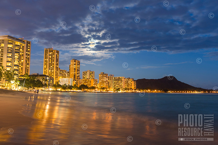 A couple in the distance walk Waikiki Beach under a full moon on O'ahu.