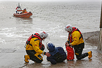 Pictured: An RNLI rescuer who poses as a casualty is rescued by coleagues on a slipway in on a beach St Donats, Wales, UK. Friday 20 April 2018 <br /> Re: The Royal National Lifeboat Institution (RNLI) and the Maritime and Coastguard Agency (MCA) have held a special media event to demonstrate how drones could be used in search and rescue activity in the future to help save lives at the Atlantic College in St Donats, south Wales, UK. <br /> The rescue scenario took place along a stretch of coastline in south Wales, featuring a drone, an RNLI lifeboat and an MCA helicopter winching the casualty to safety.