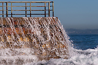 Water cascades over a brick sea wall at La Jolla Children's Pool, with its slightly rusty fence visible to the top.  A wave has just hit the wall, and white foamy water is flying over the bricks as the water crashes to the sea in front of the wall.  This contrasts with the perfectly calm blue water in the background.