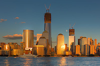 The setting sun reflects off the facades of the buildings of the World Financial Center as the waxing gibbous moon rises amidst the new buildings under construction in the World Trade Center complex, including the Freedom Tower (One World Trade Center), in New York City.