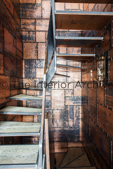 A contemporary staircase is enclosed in a  copper stairwell designed by Giancarlo Candeago