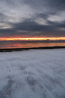 A light snow blankets Kenai Beach as a fiery sunset lights up the clouds over the Aleutian Range and Cook Inlet in Kenaii, Alaska.