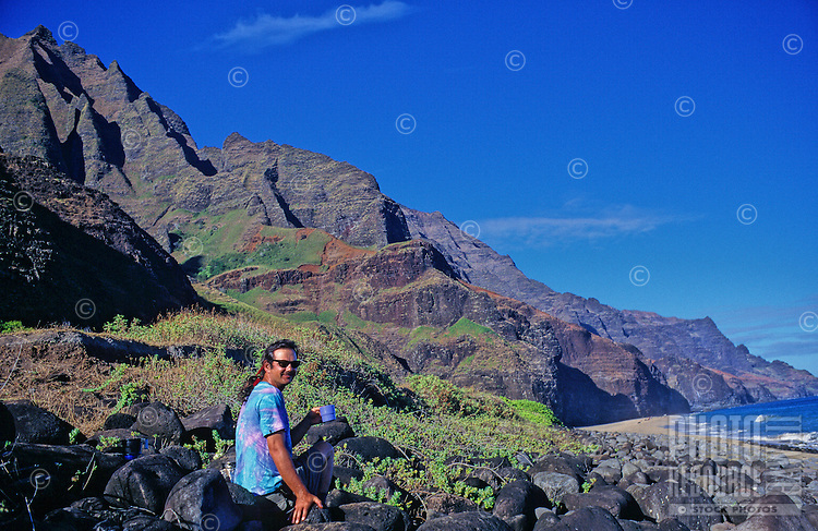 A camper has a cup of coffee on rocks near Kalalau Beach on the Na Pali Coast