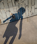 Young girls shadow outdoors on path and wall on summers day