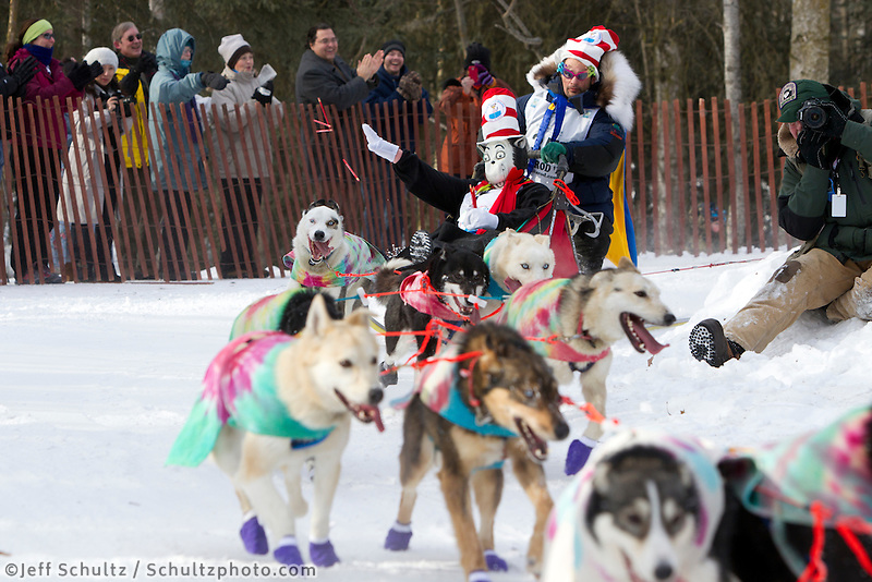 Iditarider - cat in the hat - throws pencils to the crowd as musher Hugh Neff rounds a corner on the bike trail in mid-town Anchorage during the ceremonial start of the 2011 Iditarod