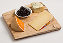 Three cheeses and cherry preserves on a cutting board