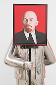 "London, UK. 25 November 2014. Installations from the series ""Paradies Lost"" by Grisha Bruskin. Grisha Bruskin stands next to his arwork Man with a portrait of Lenin. Press preview of the new exhibition Post Pop: East Meets West at the Saatchi Gallery, London. The Tsukanov Family Foundation and Saatchi Gallery present the first comprehensive exhibition examining why Pop Art has had such a powerful influence over artists from world regions that had or still have very different and sometimes opposing ideologies. The exhibition brings together 250 works by 110 renowned artists from China, the Former Soviet Union, Taiwan, the UK and USA in the largest survey to date exploring Pop Art's enduring legacy. The exhibition is open to the public from 26 November 2014 to 23 February 2015, admission is free. Photo: Bettina Strenske"