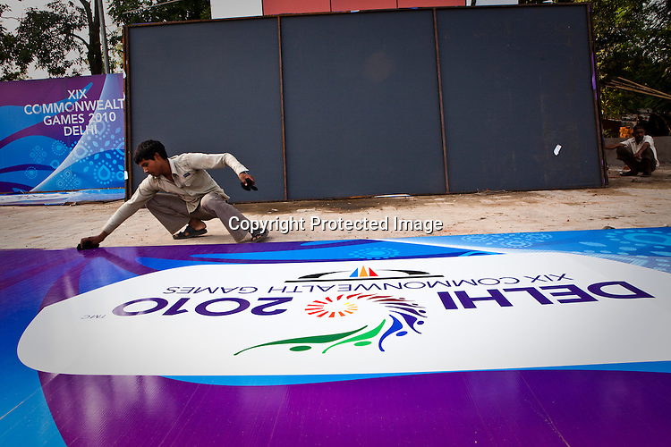 An Indian worker cleans a Commonwealth Games hoarding in New Delhi, India.