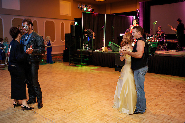 Arnold Schwarzenegger impersonators dance at the Sunburst Charity Ball during the Sunburst Convention of Professional Tribute Artists