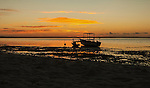 A traditional boat is silhouetted at sunrise on the lagoon on the remote island of Kiritimati in Kiribati