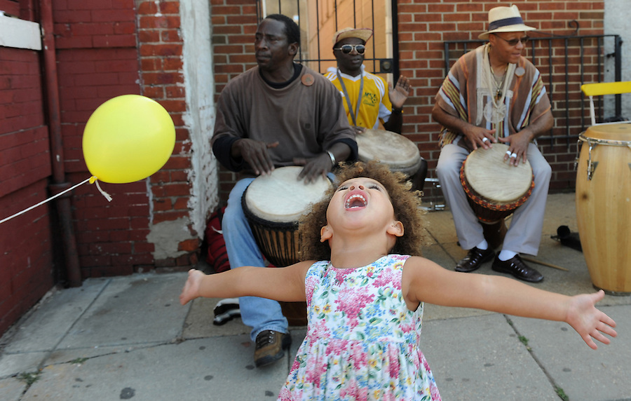 Lucy Hill, 3, of Washington, DC, dances to the music of the Malcolm X Drummers (left to right) Butch Jackson, Baba Joseph Ngwa and Doc Powell during the H St. Festival in Washington, DC. The festival brings the developing community together through the celebration of artists and musicians.