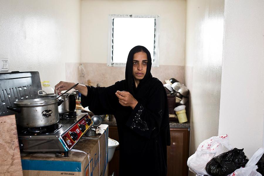 Gaza, Khuzaa: la fille de Feda fait &agrave; manger &agrave; l'int&eacute;rieur de leur petite cuisine de leur conteneur. La salle est assez pour eux, mais d'autres familles de 10 personnes vivant &eacute;galement dans un conteneur manquent d'espace.<br /> <br /> Gaza, Khuzaa: Feda's daughter is cooking inside their small kitchen of their container. The room is enough for them but other families of 10 people living in a container as well lack of space.